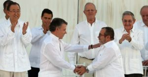Colombia's President Juan Manuel Santos, left, and the top commander of the Revolutionary Armed Forces of Colombia (FARC) Rodrigo Londono, known by the alias Timochenko shake hands after sign a peace agreement between Colombia's government and the FARC in Cartagena, Colombia, Monday, Sept. 26, 2016. (AP Photo/Fernando Vergara)
